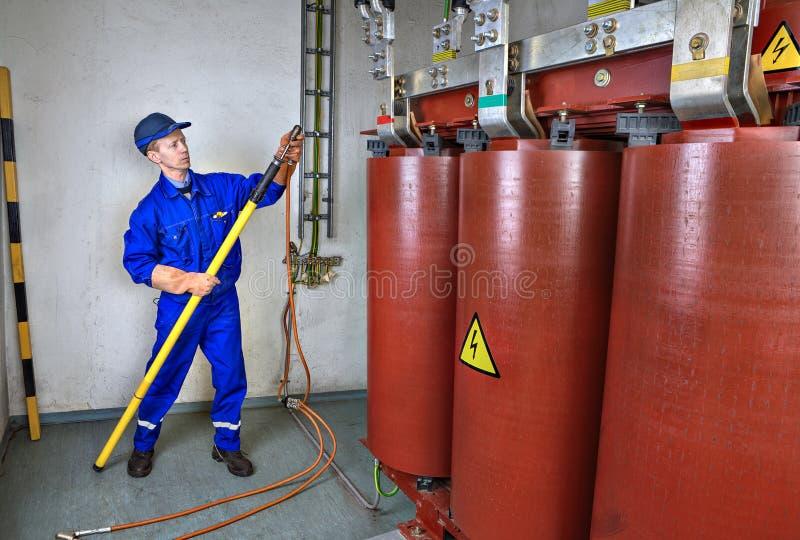 L'elettricista utilizza un bastone caldo al trasformatore della terra fotografia stock