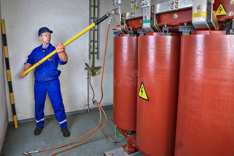 L'elettricista utilizza un bastone di scarico al trasformatore della terra immagine stock