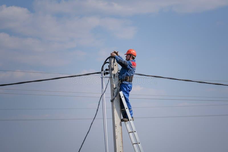 L'elettrotecnico esegue i collegamenti su un alto palo che sta sulle scale lavoro elettrico di palazzo multipiano casa del podklu fotografie stock libere da diritti