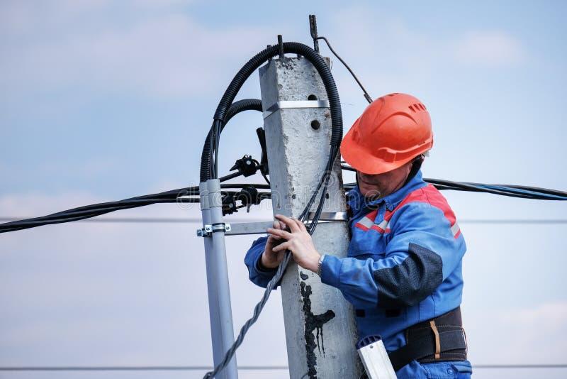 L'elettrotecnico esegue i collegamenti su un alto palo che sta sulle scale lavoro elettrico di palazzo multipiano casa del podklu fotografia stock libera da diritti