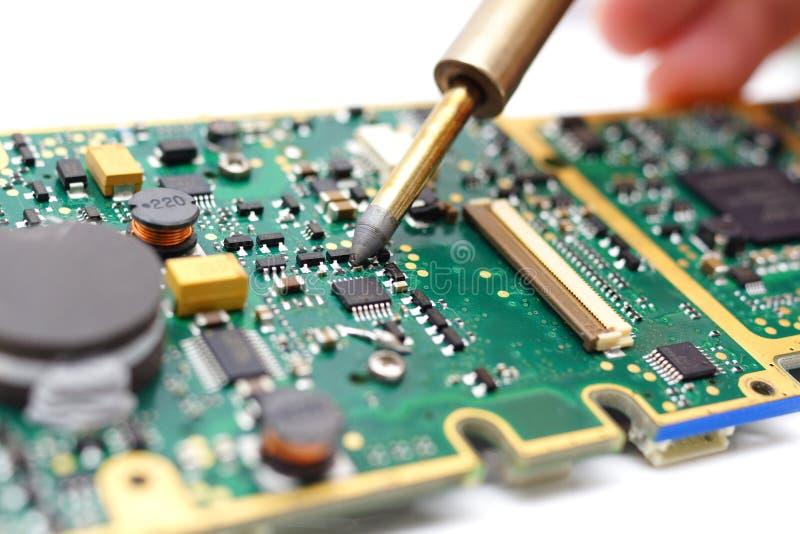 L'elettrotecnico sta saldando sul circuito stampato fotografia stock libera da diritti