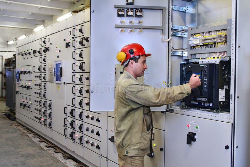 L'elettrotecnico utilizza l'attrezzatura del centralino fotografie stock libere da diritti