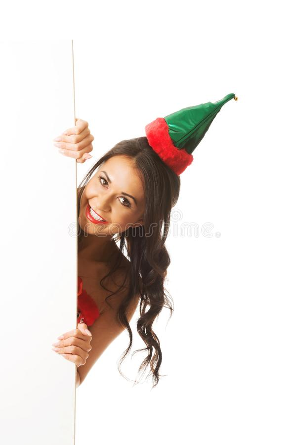 L'elfe de port de femme vêtx la dissimulation derrière la bannière blanche, regardant l'appareil-photo photographie stock libre de droits