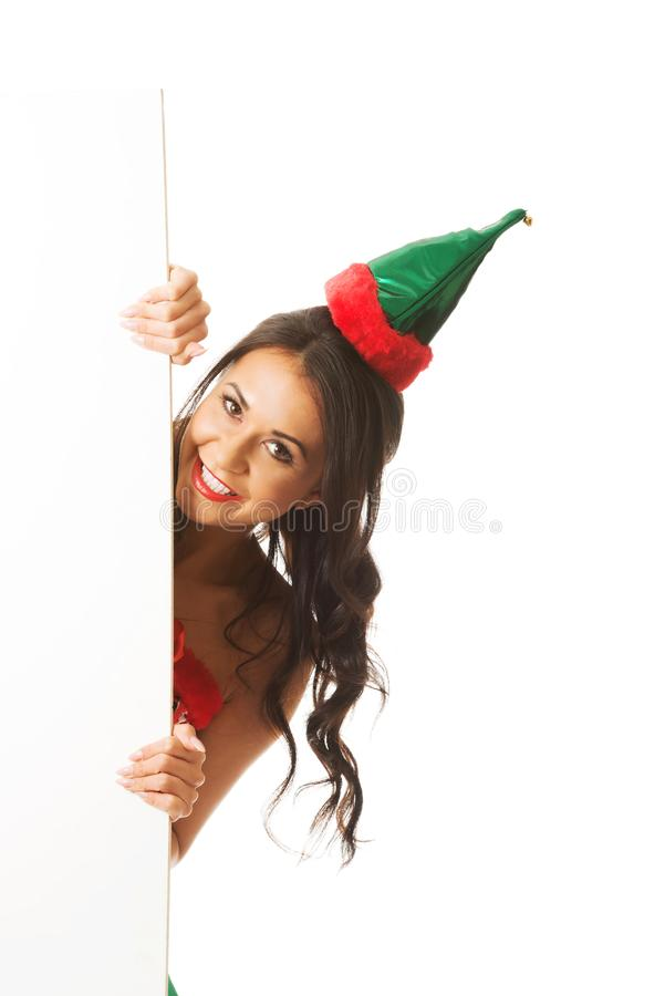 L'elfe de port de femme vêtx la dissimulation derrière la bannière blanche, regardant l'appareil-photo photographie stock