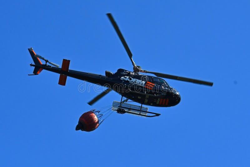 L'elicottero del pompiere durante l'operazione di salvataggio raccoglie l'acqua dentro fotografie stock libere da diritti