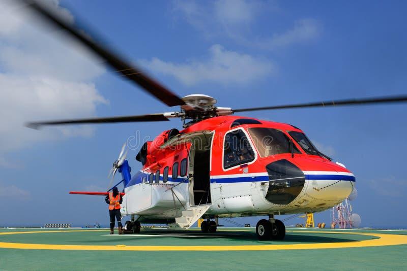 L'elicottero sta atterrando per imbarcare il passeggero al platfor dell'impianto offshore fotografia stock
