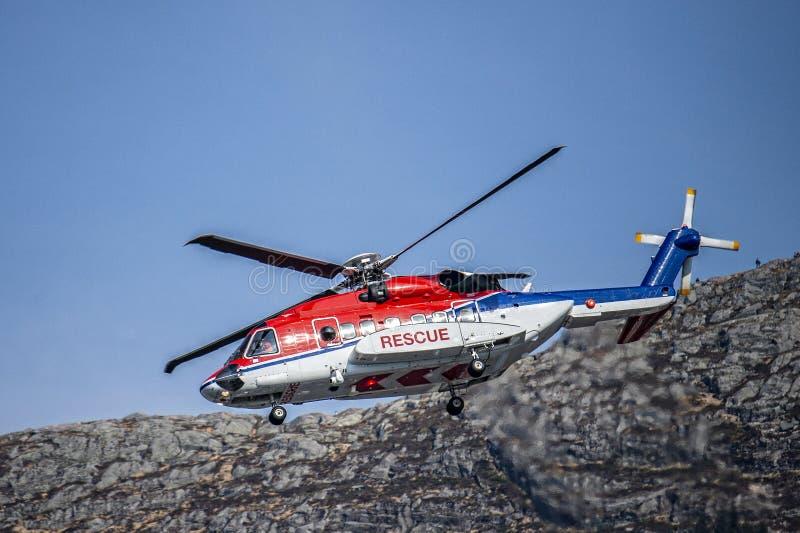 L'elicottero tricolore di salvataggio in rosso, in bianco e blu scende per atterrare fotografie stock libere da diritti