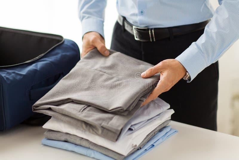 L'emballage d'homme d'affaires vêtx dans le sac de voyage images libres de droits