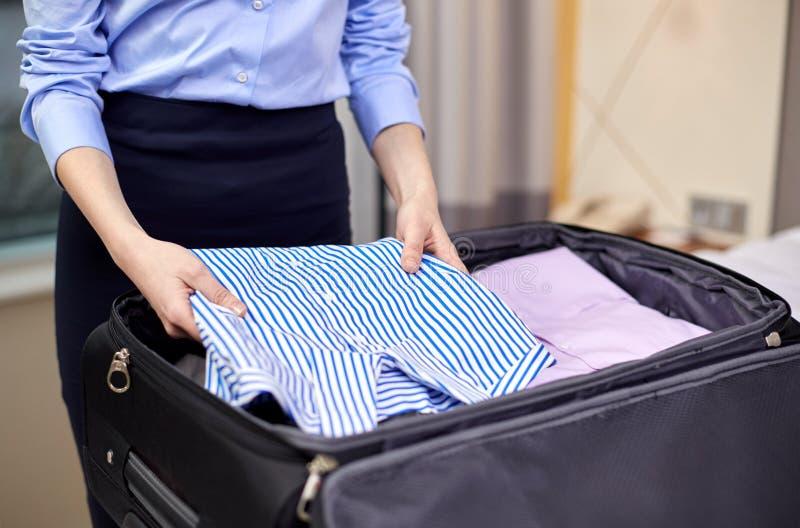 L'emballage de femme d'affaires vêtx dans le sac de voyage photographie stock