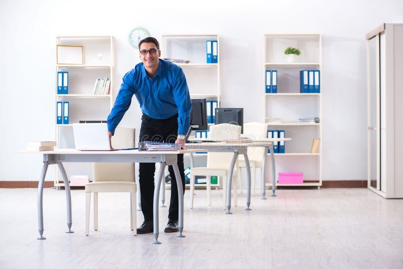 L'employé bel d'homme d'affaires s'asseyant à son bureau dans le bureau image libre de droits