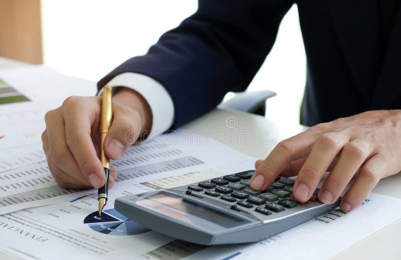 L'employé de bureau à l'aide de la calculatrice et le stylo analysent des graphiques images stock