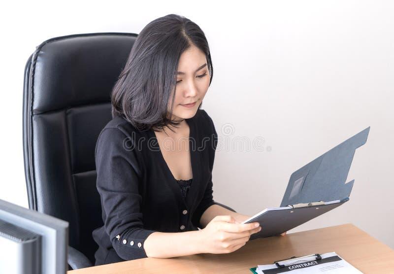 L'employé de bureau asiatique féminin vérifie le rapport images stock