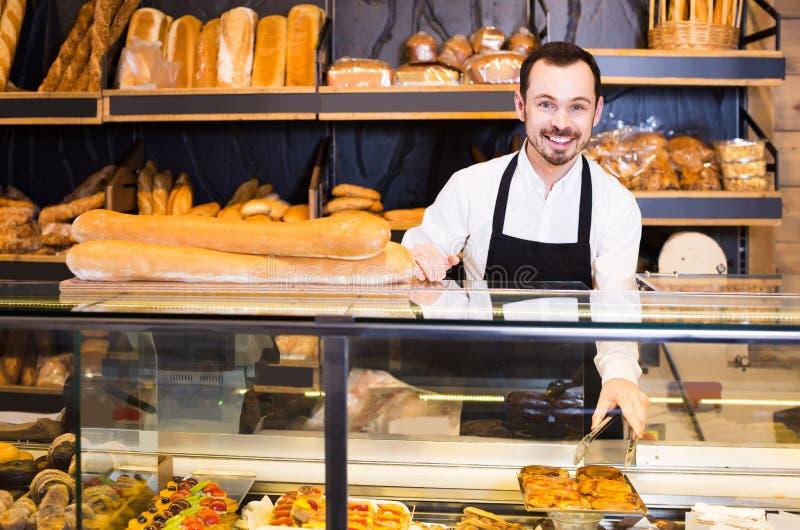 L'employé de magasin masculin démontrant la pâtisserie délicieuse fraîche font cuire au four dedans image libre de droits
