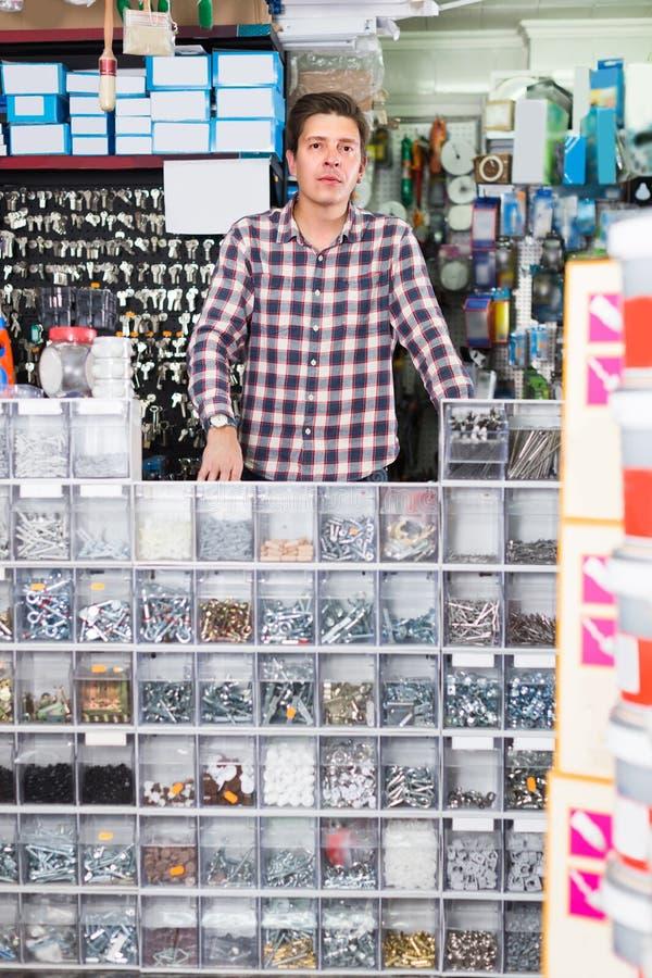 L'employé masculin dans le magasin de matériel exploite des marchandises le constructio image stock