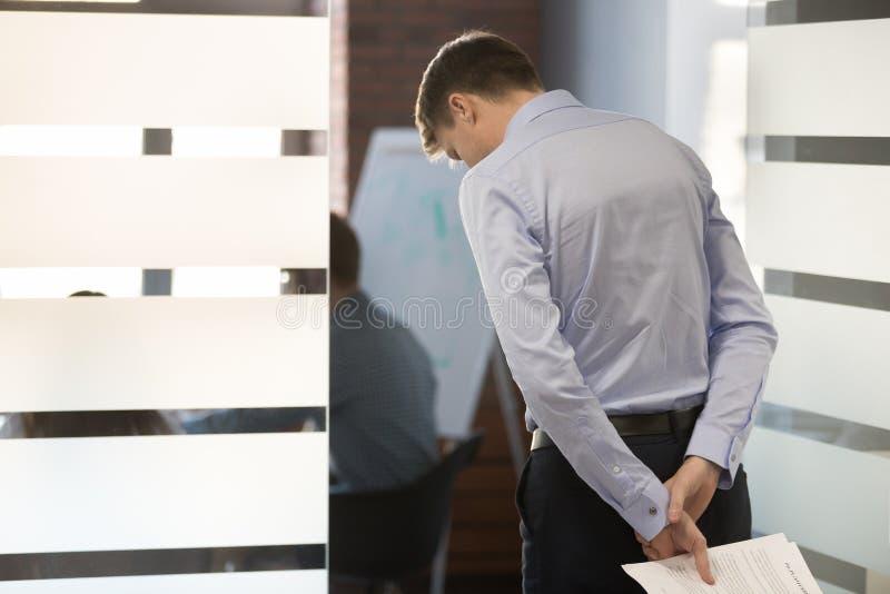 L'employé masculin nerveux effrayé entrent dans le lieu de réunion de rédiger le rapport photo stock