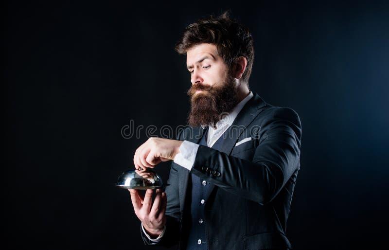 L'employé portent la cloche métallique L'homme a bien toilett? le costume formel de monsieur pour tenir peu de cloche Portion et  image stock