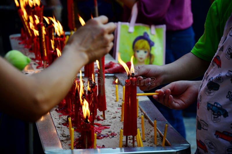 L'encens brûlant de personnes et la bougie rouge pour prie un dieu image stock