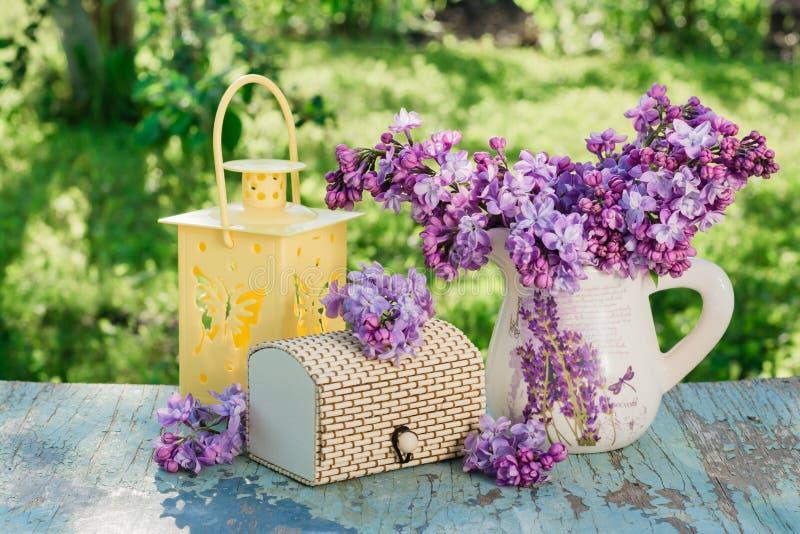 l'Encore-vie avec un lilas dans une cruche, un cercueil, une lampe-torche sur une table en bois photos libres de droits