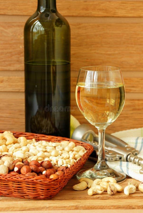 l'Encore-vie avec un verre de vin et d'écrous photos stock