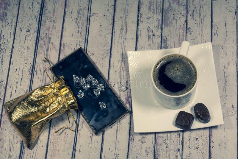 l'Encore-vie une tasse de café noir, un petit sac, pierres en verre, sucrerie, téléphone sur un fond clair image libre de droits