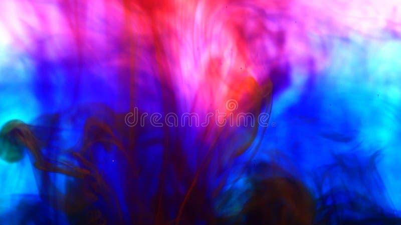 L'encre liquide bleue et rouge de fond coloré lumineux colore le mélange dans l'eau image libre de droits