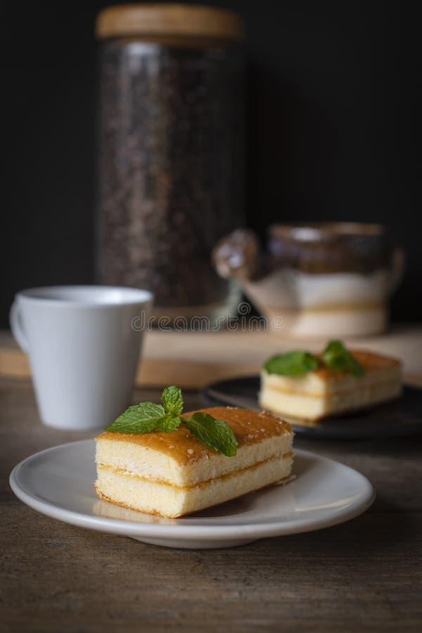 L'endroit à la vanille de gâteau de couche sur le plat blanc sur la table en bois là sont la tasse blanche et le plat noir et le  images libres de droits