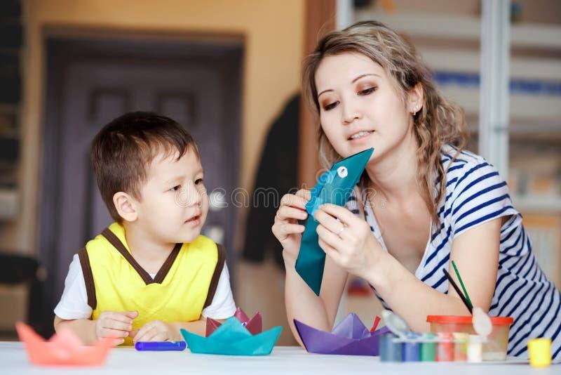 L'enfance curieux, un petit garçon jouant avec sa mère, dessine, des peintures sur les paumes images libres de droits