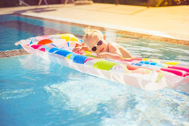 L'enfant éclabousse sur un matelas coloré gonflable dans la piscine photos stock
