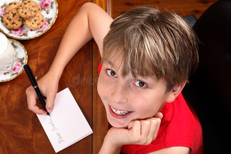L'enfant écrit une lettre ou une carte photo libre de droits