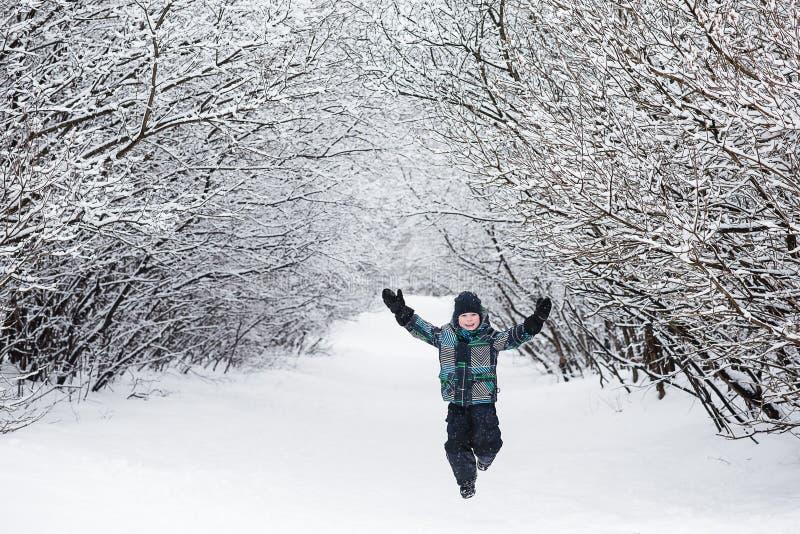 L'enfant apprécie l'hiver et jouer avec la neige photos libres de droits