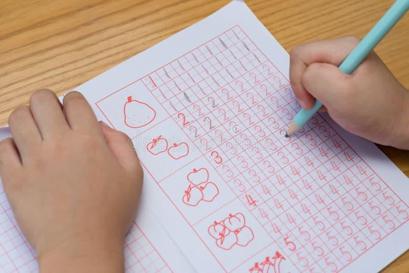 L'enfant apprend à écrire des chiffres arabes par le guide suivant photo libre de droits