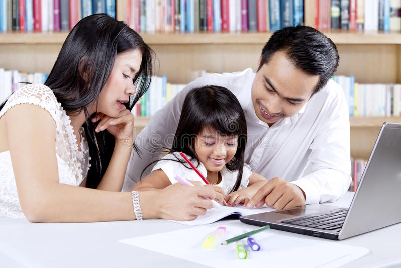 L'enfant apprend avec ses parents dans la bibliothèque images libres de droits