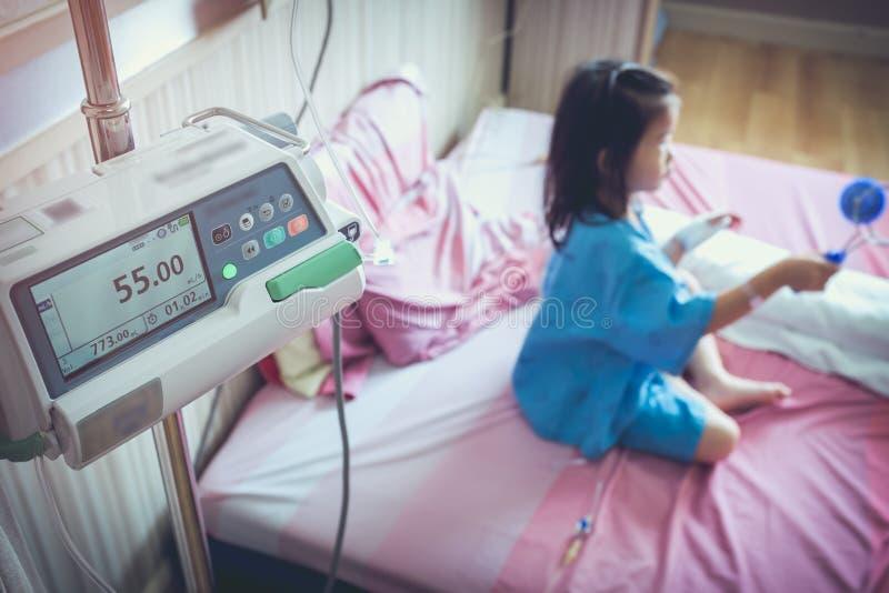 L'enfant asiatique de maladie admis avec l'iv salin s'égouttent en main photographie stock libre de droits