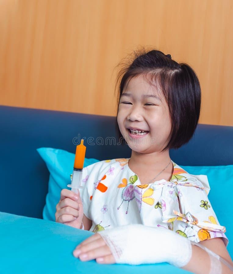 L'enfant asiatique de maladie a admis dans l'h?pital avec intraveineux salin en main image stock