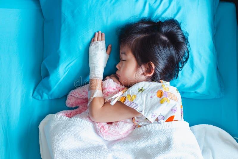 L'enfant asiatique de maladie a admis dans l'h?pital avec intraveineux salin en main photographie stock libre de droits