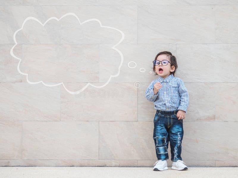 L'enfant asiatique de plan rapproché indiquent quelque chose action avec la zone de texte sur le fond texturisé de marbre de mur  photographie stock