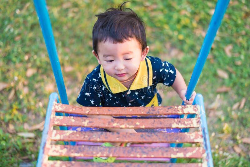 L'enfant asiatique monte les escaliers en parc Concept de grandir images libres de droits