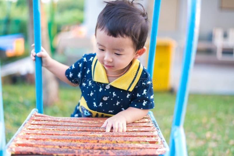 L'enfant asiatique monte les escaliers en parc Concept de grandir photo libre de droits