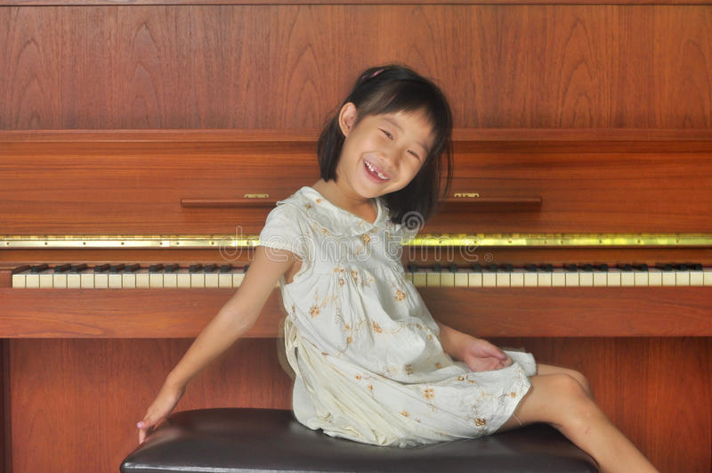 L'enfant asiatique s'assied devant le piano photo libre de droits