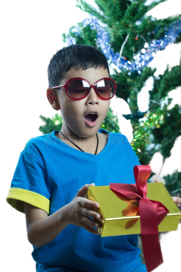 L'enfant asiatique sur des lunettes de soleil étonnent pour avoir le cadeau de Noël photos stock
