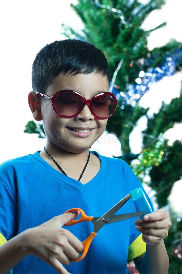 L'enfant asiatique sur des sunglass essayent d'ouvrir son présent avec des ciseaux image libre de droits