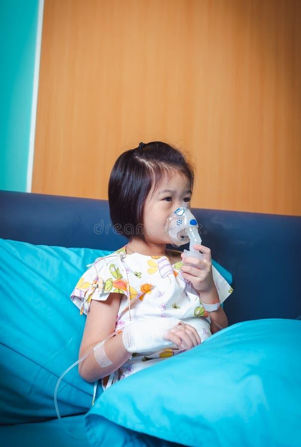L'enfant asiatique triste tient un inhalateur de vapeur de masque pour le traitement de l'asthme respiration par un n?buliseur de photo stock