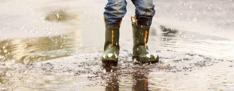 L'enfant avec des bottes de pluie saute dans un magma images stock