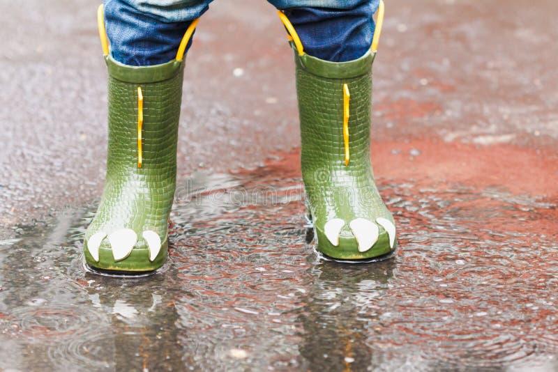 L'enfant avec des bottes de pluie saute dans un magma images libres de droits