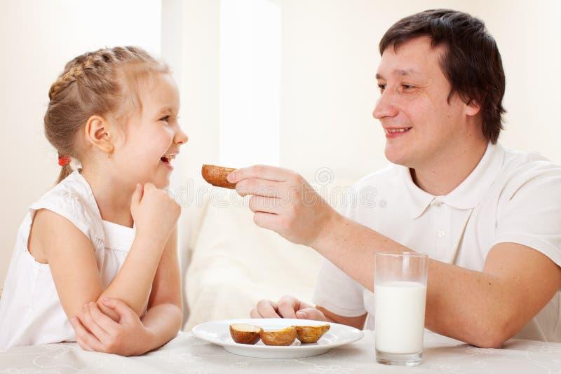 L'enfant avec le père prennent un petit déjeuner photos stock