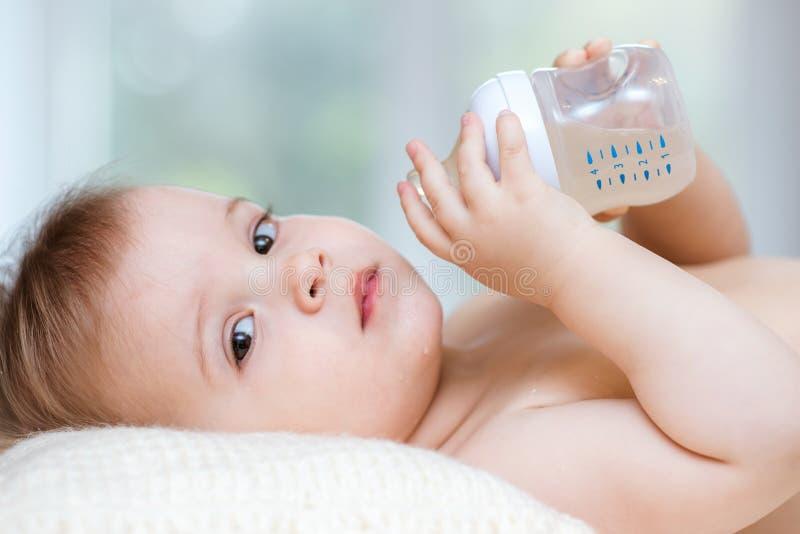 L'enfant boit de la compote d'une bouteille ? la maison photographie stock