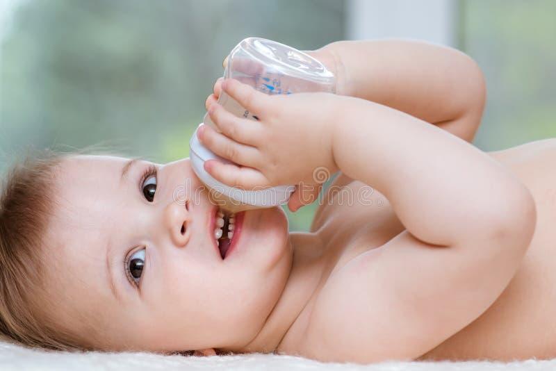 L'enfant boit de la compote d'une bouteille ? la maison photographie stock libre de droits