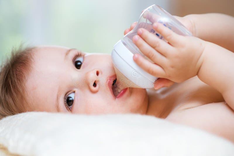 L'enfant boit de la compote d'une bouteille ? la maison images stock