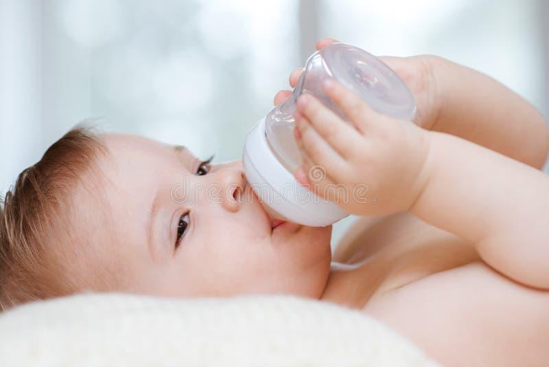 L'enfant boit de la compote d'une bouteille ? la maison image stock