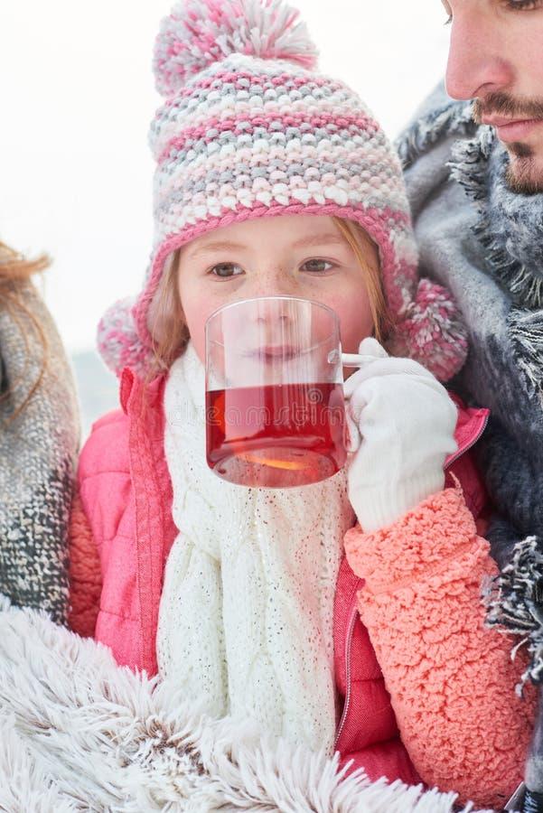L'enfant boit du thé en hiver photographie stock